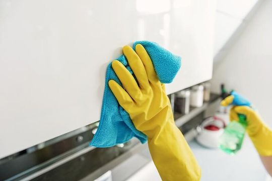 A person cleaning using a cloth